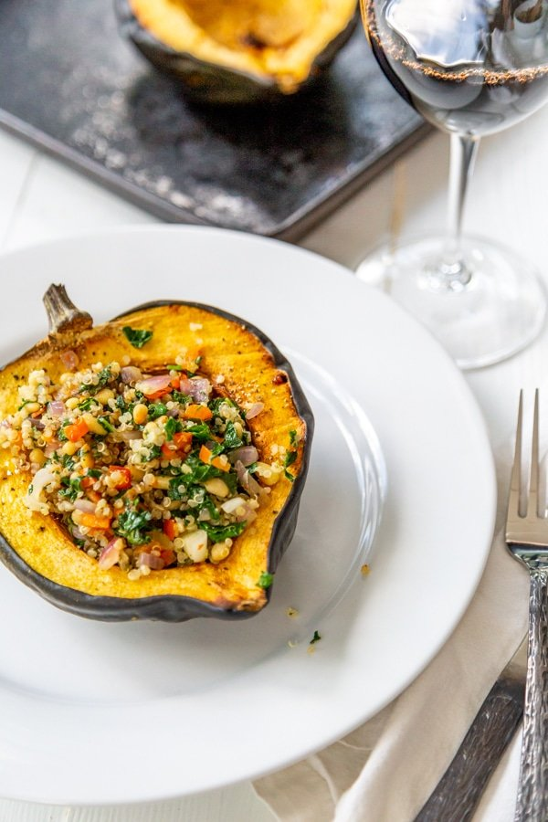 Stuffed acorn squash on a white plate with squash in the background.