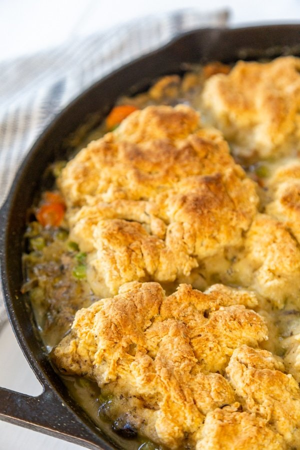 An iron skillet with chicken and biscuits.