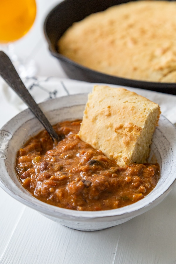 A bowl of chili with a slice of cornbread and a spoon in the bowl.
