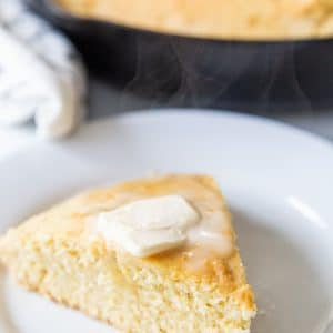 A slice of cornbread with butter on top on a white plate and a skillet of the cornbread behind it.
