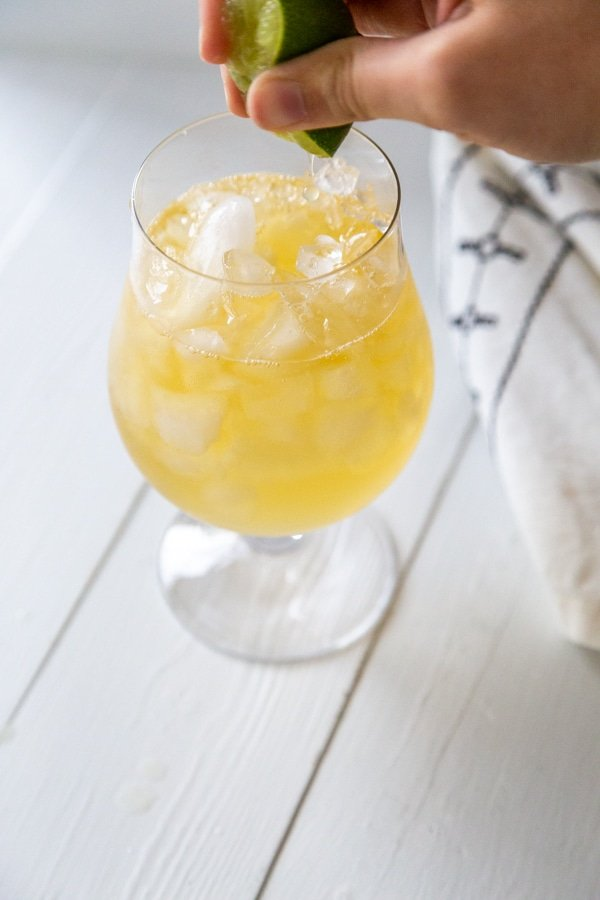 A hand squeezing a lime over a glass of ginger beer and rum.