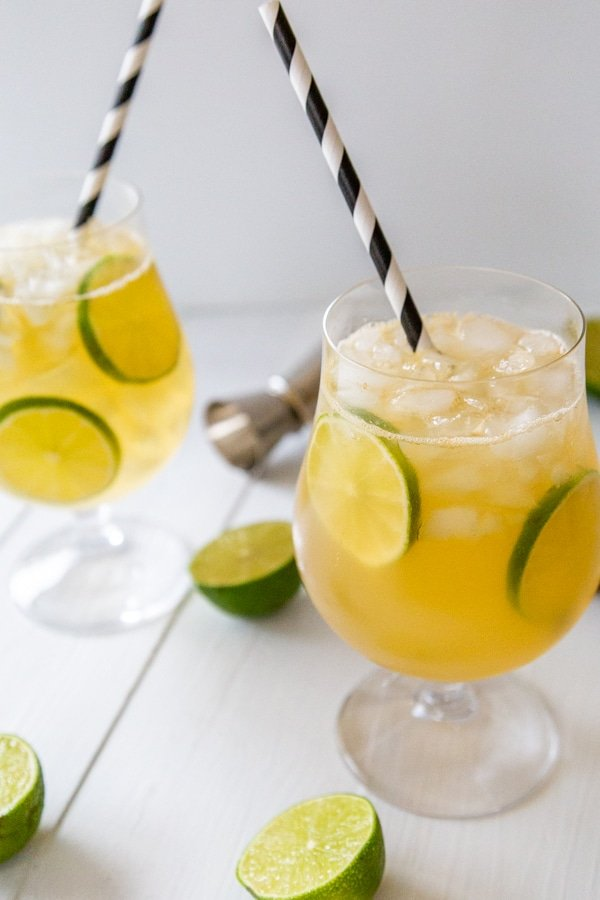 Two cocktails on ice with lime wheels and black and white straws.