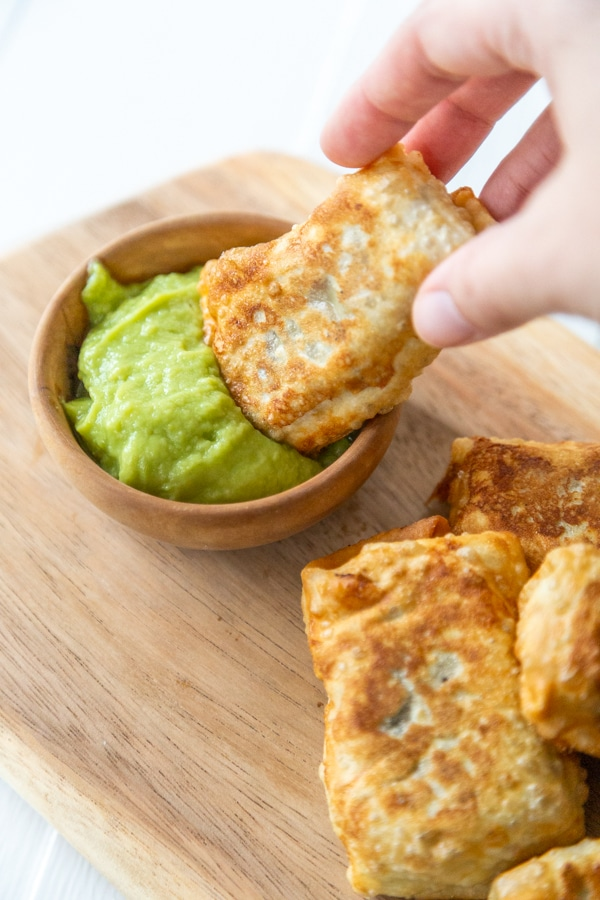 A hand dipping an egg roll into a wood bowl of green dipping sauce.