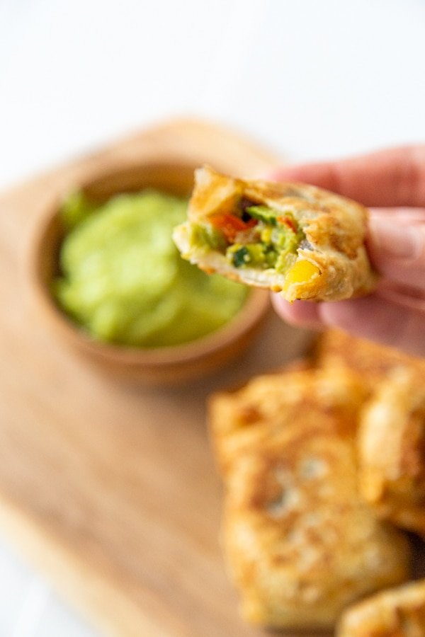 A hand holding an egg roll with a bite taken out of it over a wood board with more rolls and green sauce.