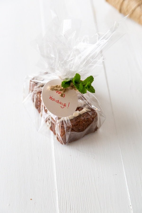 A chocolate loaf cake wrapped in cellophane with a ribbon and sprig of mint.