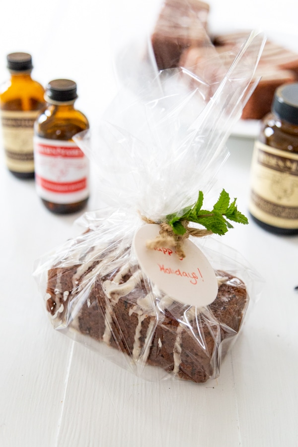 A mini chocolate cake loaf wrapped in cellophane and a ribbon with a sprig of mint, and Nielsen-Massey Vanillas extract bottles next to it.