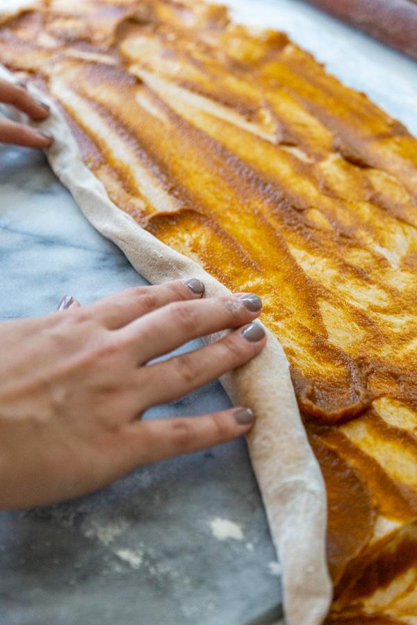 Hands rolling a rectangular piece of dough with pumpkin filling.
