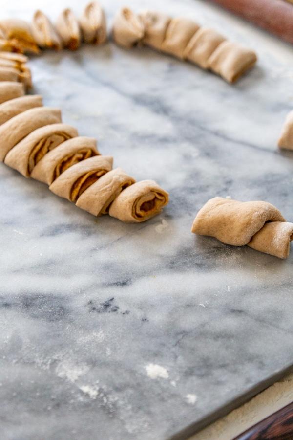 Sliced dough for pumpkin cinnamon rolls on a marble surface.