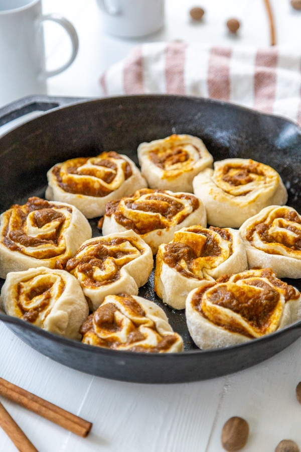 Pumpkin cinnamon rolls in an iron skillet.