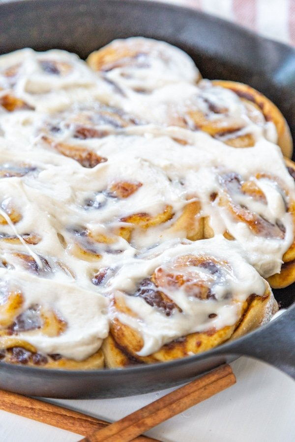 An iron skillet with frosted cinnamon rolls.