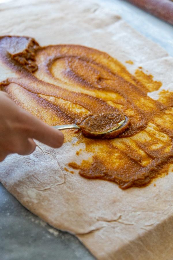 A hand spreading pumpkin filling on a rectangular piece of dough.