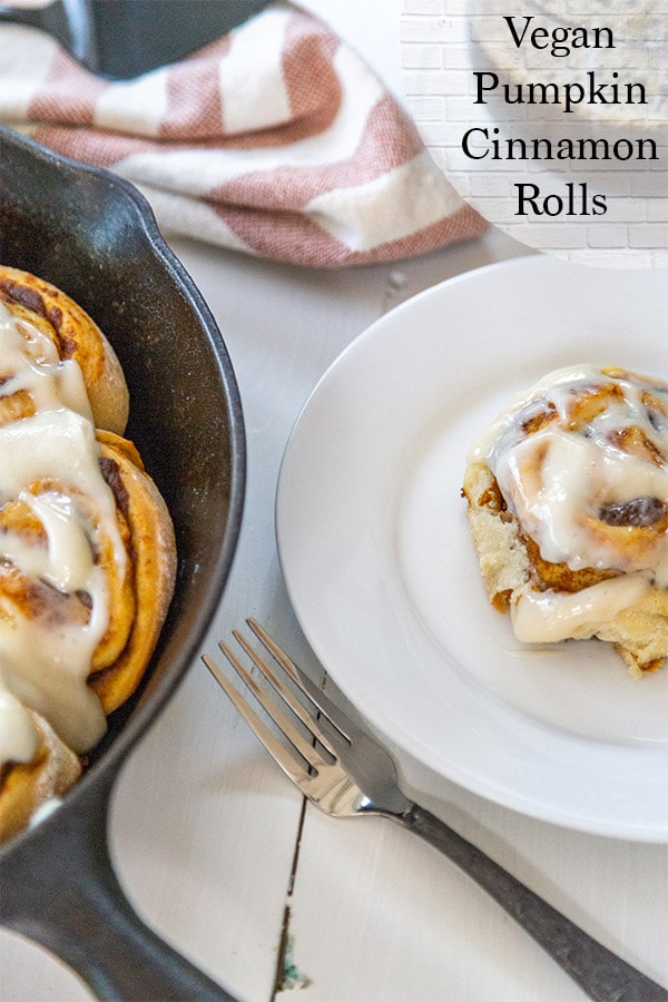 An iron skillet with cinnamon rolls and a white plate with a roll.