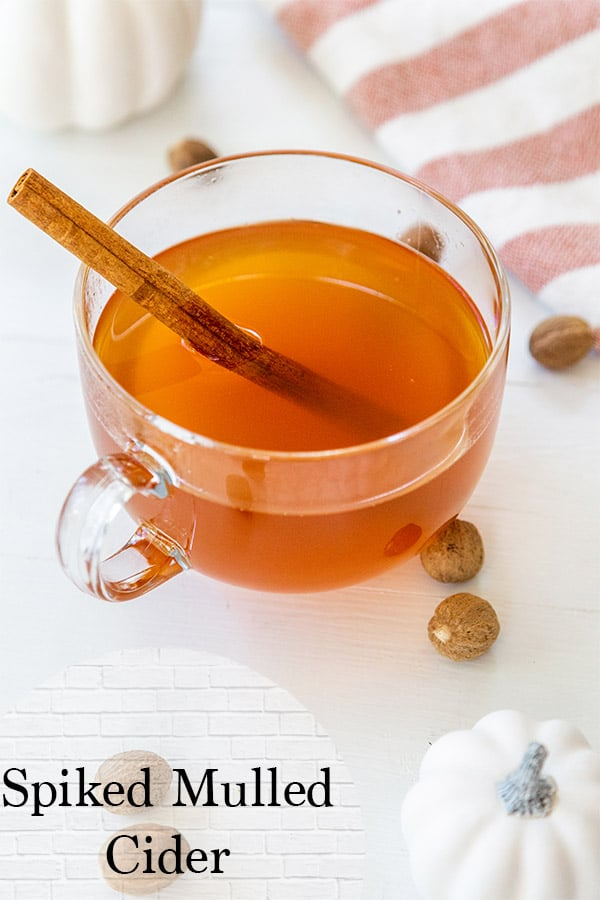 mulled spiked cider in a glass mug with a cinnamon stick, pumpkins, nutmeg, and an orange and white striped towel