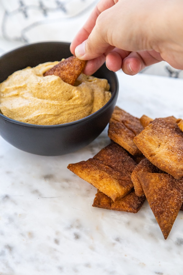 A hand dipping a pie crust chip into a black bowl of pumpkin dip.