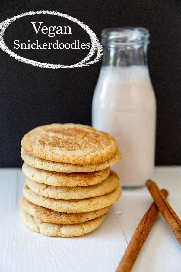 vegan snickerdoodle recipe with bottle of almond milk behind a stack of vegan snickerdoodles