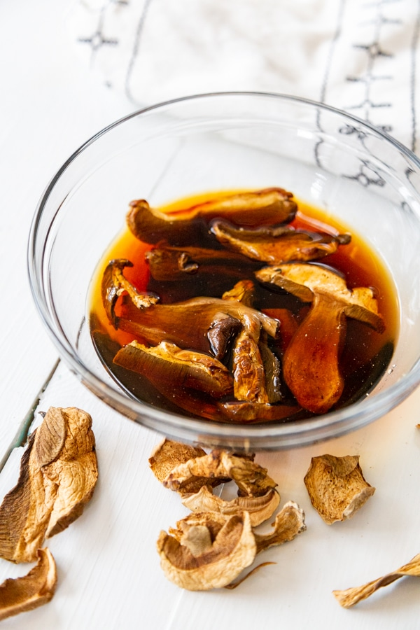 A clear glass bowl of dried porcini mushrooms in water.