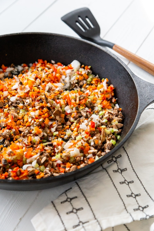 An iron skillet with seared veggies and a black and white towel and spatula next to the pan.