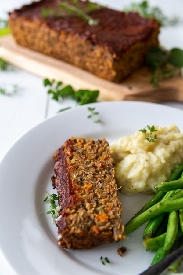 A slice of lentil loaf with green beans and mashed potatoes on a white plate with the whole loaf in the background.