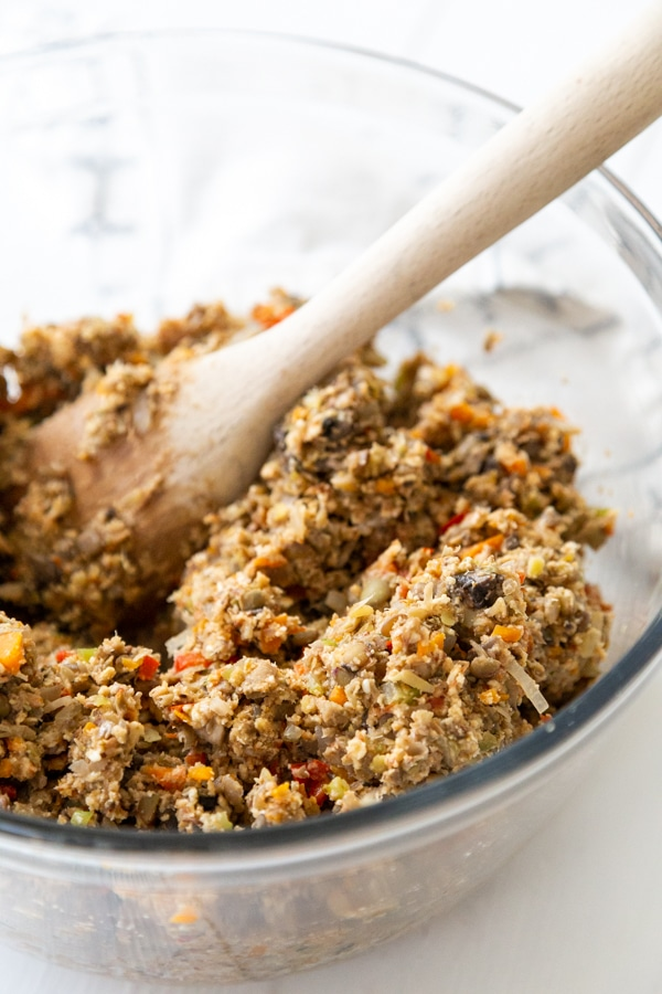 A clear glass bowl with a lentil loaf mixture being stirred with a wooden spoon.