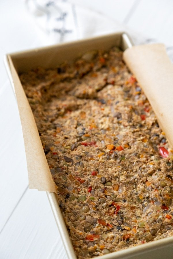 An unbaked lentil loaf in a bread pan with parchment paper.