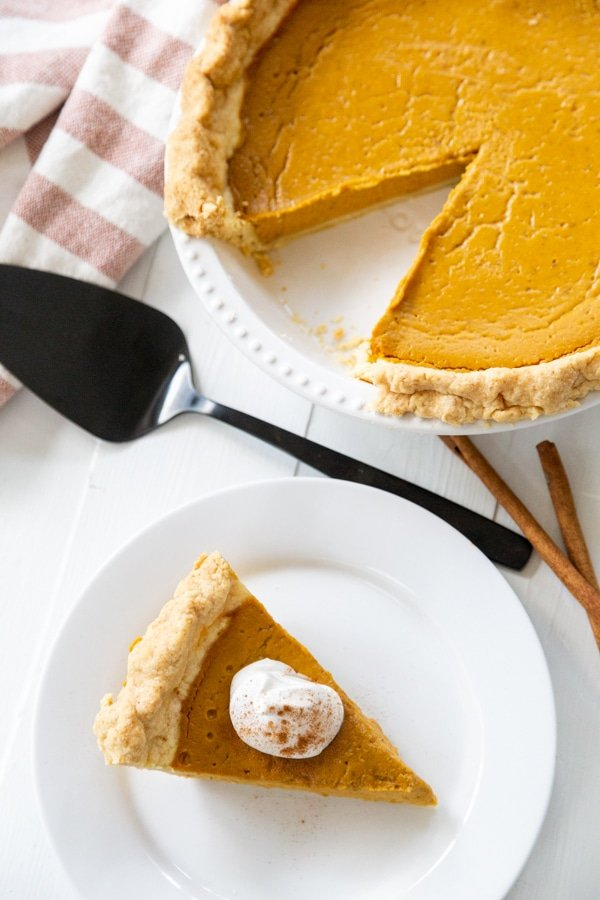 A slice of pumpkin pie with whipped topping on a white plate and the whole pie next to it.