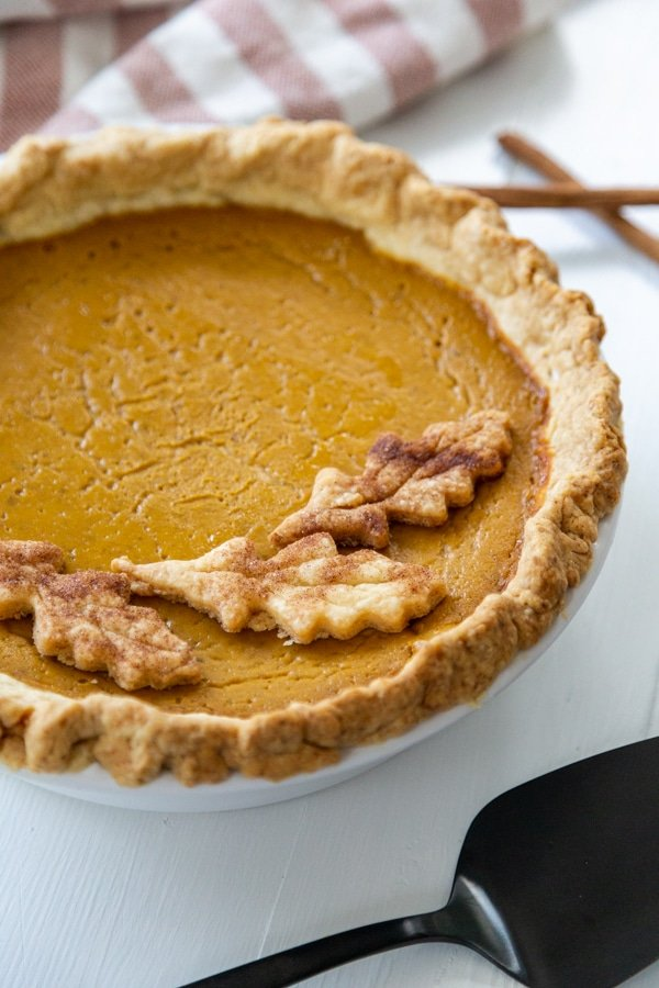 A pumpkin pie with pie crust leaves on top and a black pie spatula.