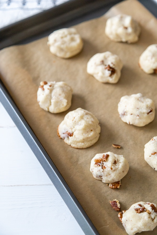 A cookie sheet with parchment paper and unbaked Russian Tea Cake cookies.