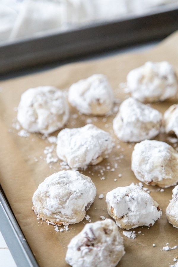 A cookie tray of Russian Tea Cakes on parchment paper.