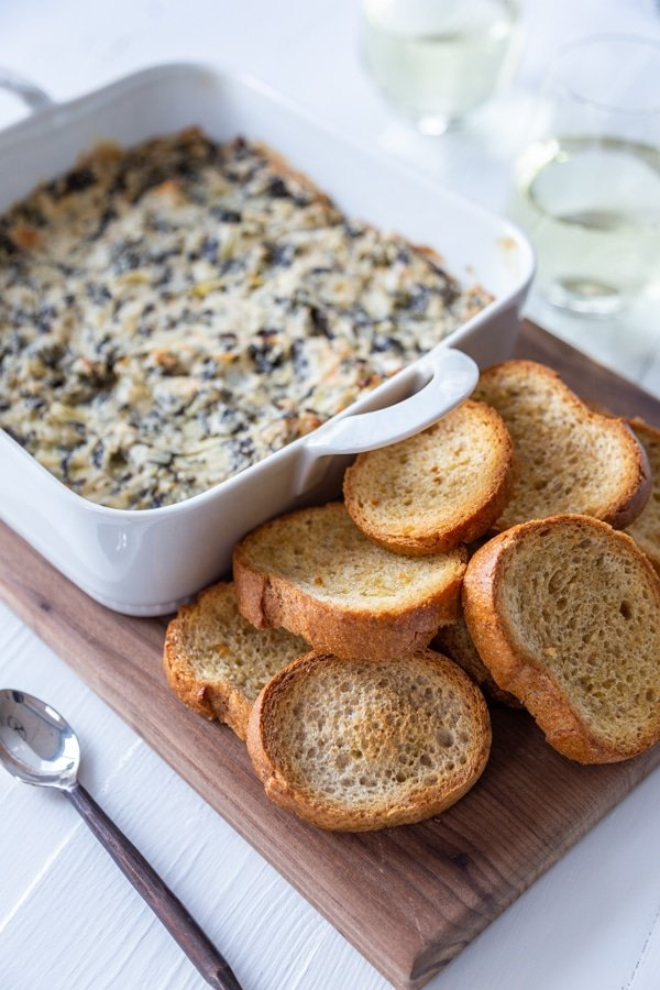 A wood board with pieces of toast and a white dish of spinach artichoke dip.