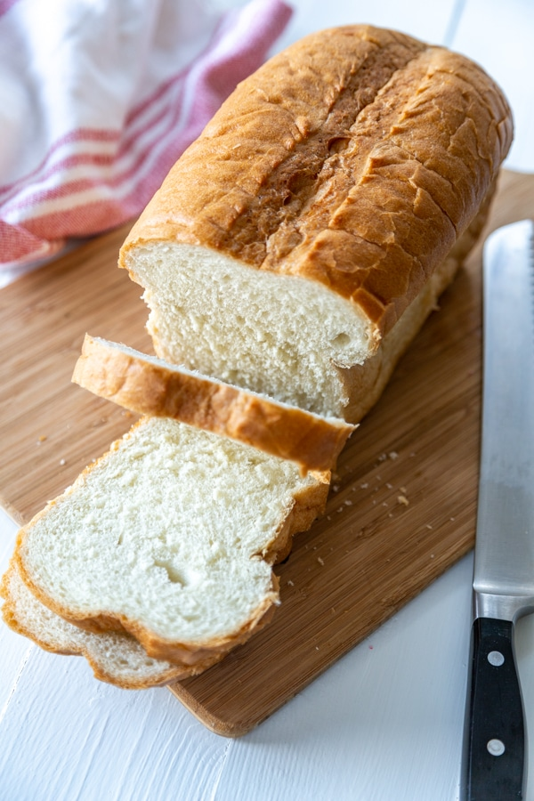 A loaf of white bread with 2 slices cut off the end.