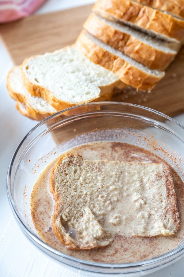 A slice of bread dipped into a bowl of milk and spices.