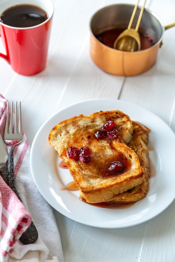 A plate of French toast with maple syrup and cranberries and a red cup of coffee and a copper pot of syrup.
