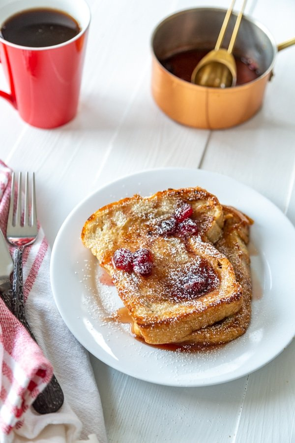 A white plate with 2 pieces of French toast with cranberry maple syrup and a copper pot with syrup and a red mug of coffee.