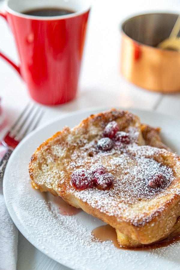 A white plate with French toast and cranberry syrup and a red mug of coffee.