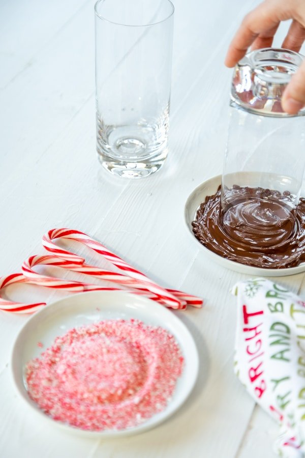 A hand dipping the rim of a glass in melted chocolate and a plate of ground candy cane.