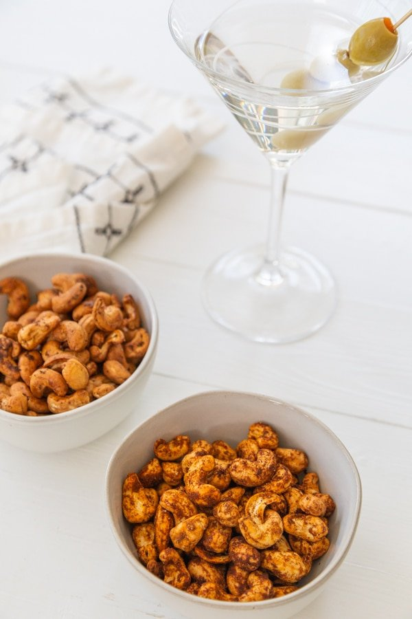 Two white bowls of spiced roasted nuts and a glass of martini.