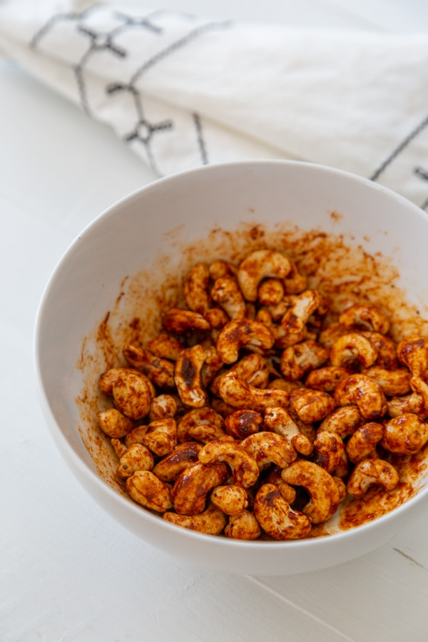 A white bowl with spiced cashews.