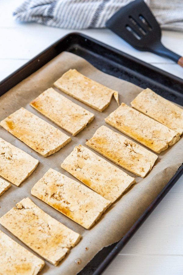 A baking sheet with parchment paper and marinated tofu strips.