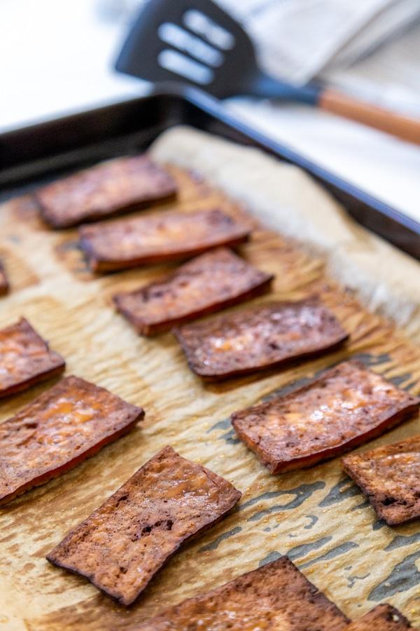 A baking sheet with tofu bacon.