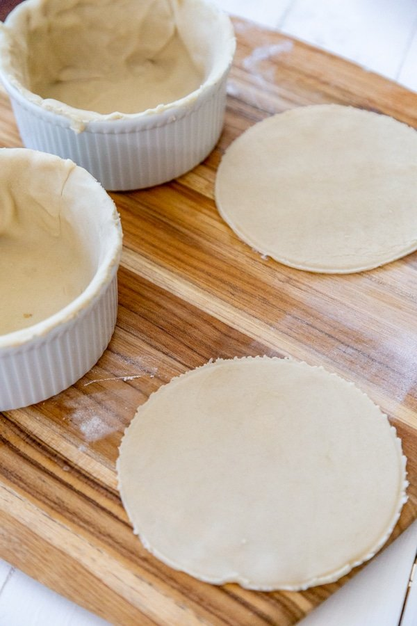 2 bowls lined with pie crust and 2 pie dough circles next to the white bowls.