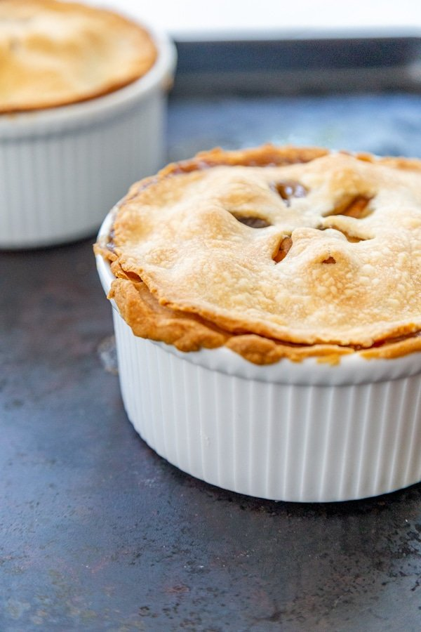 Two pot pies in white bowls.