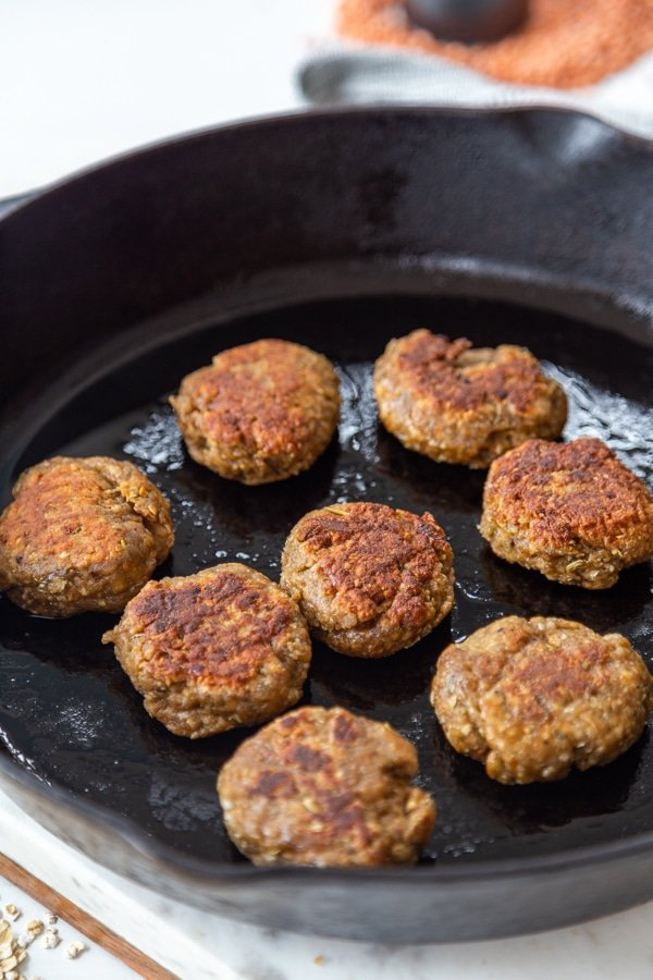 An iron skillet with breakfast sausage patties.
