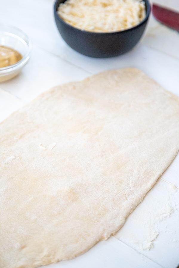 A long rectangular piece of dough on a white board.