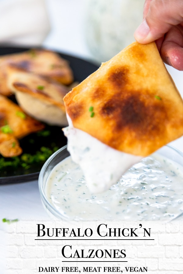 A Pinterest pin for vegan buffalo calzones with a picture of a hand dipping a calzone in ranch dressing
