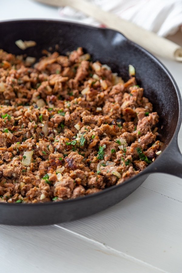 An iron skillet with ground meat and herbs.