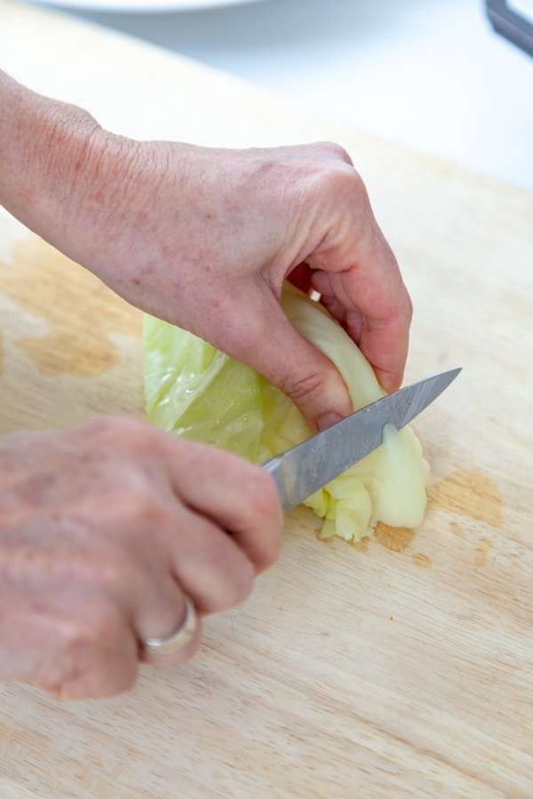 Two hands holding a cabbage leaf and a knife.