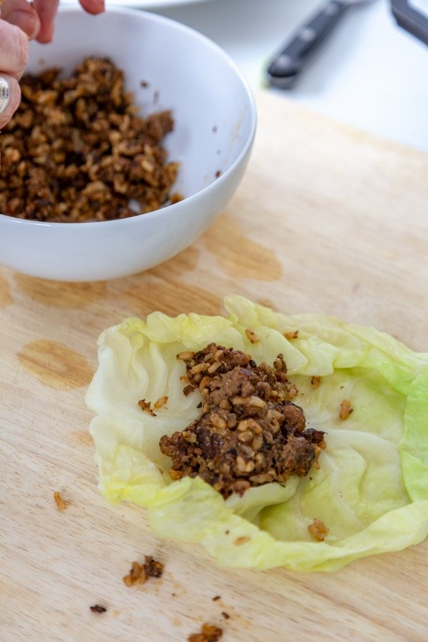Meat filling in the middle of a cabbage leaf and a white bowl of filling next to it.