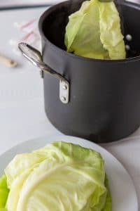 Silver tongs removing a cabbage leaf from a pot of water and a white plate with cabbage leaves is next to the pot.