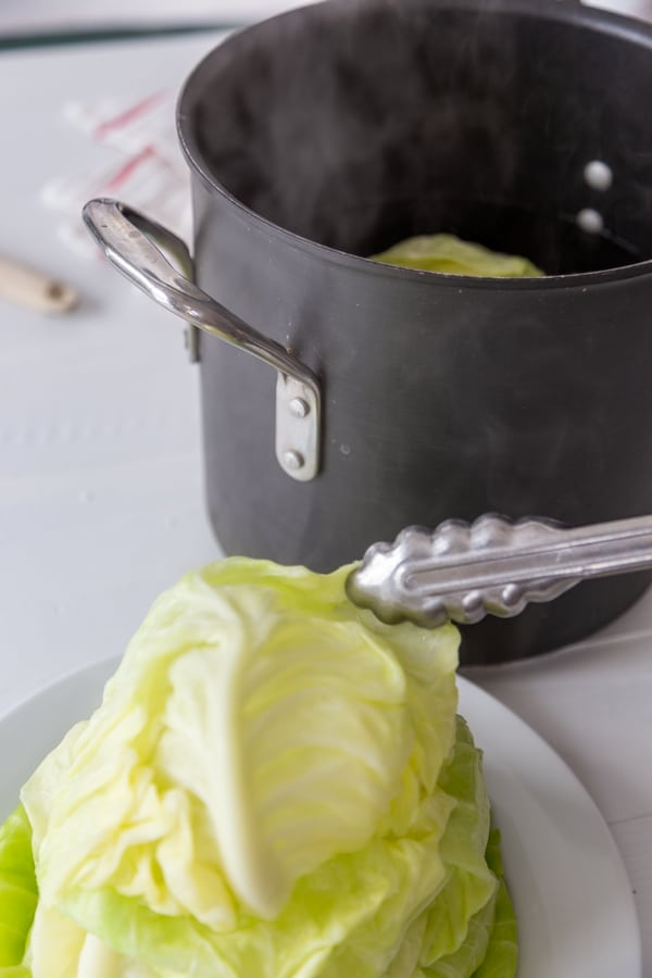 Silver tongs putting a cabbage leaf on a white plate piled with cabbage leaves.