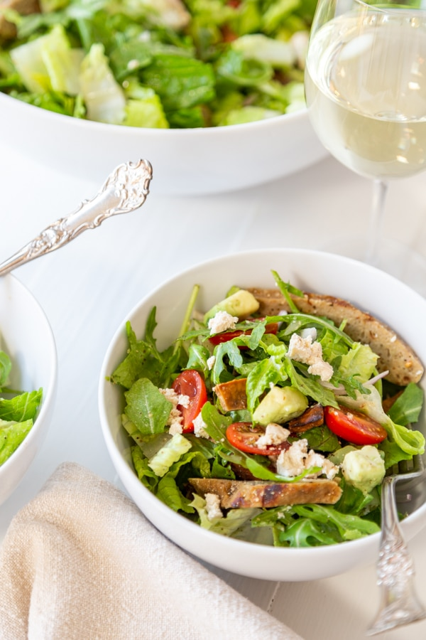 A white bowl with a Cobb salad and a large white bowl behind it with more salad.